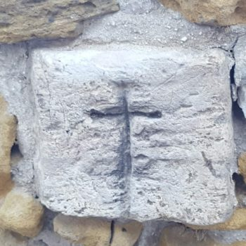 Cruz tallada en una de las piedras de la muralla